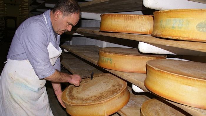 """A la Coopérative du Beaufortain, le fromager fait """"sonner"""" les meules."""